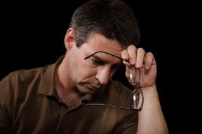 Man depressed holding glasses