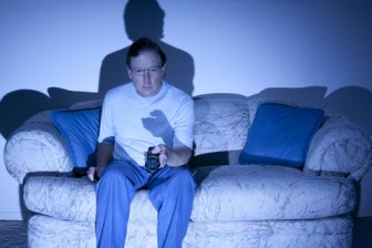 Man on sofa with tv remote